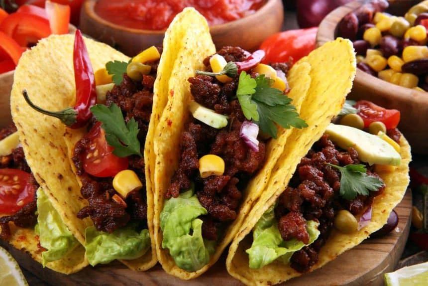Mexican cooking: tacos with beef, tomatoes, avocado, chilli and onions